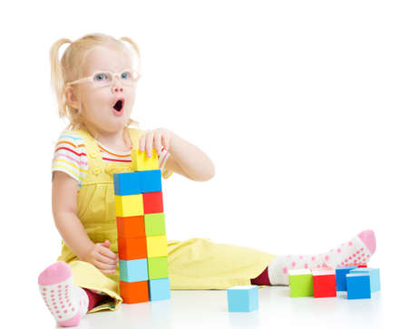 Funny kid in eyeglases making tower using blocks with letters isolated on white photo
