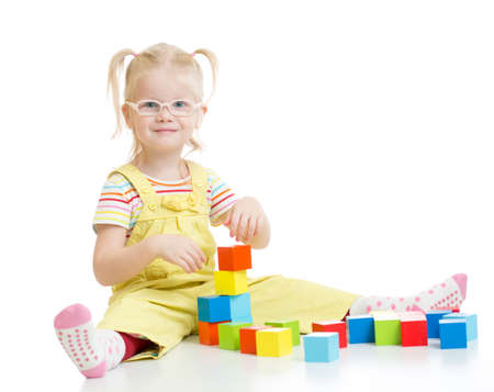 Funny kid in eyeglases making tower using blocks isolated on white photo
