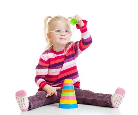 hyperopia: Bambino divertente in occhiali da vista che giocano giocattolo colorato piramide isolata su bianco