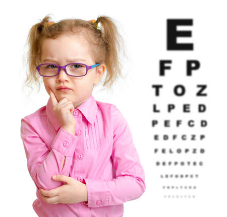 poor eyesight: Serious girl in glasses with eye chart isolated