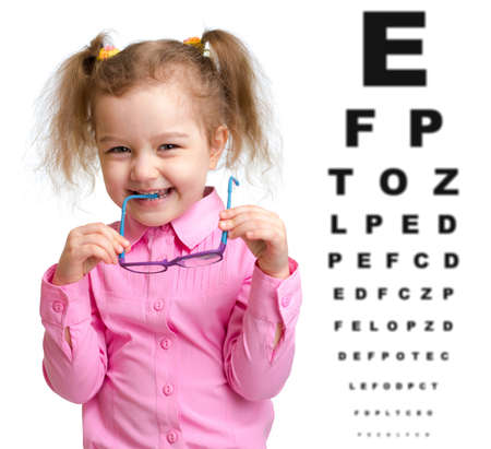 hyperopia: Smiling girl took off glasses with blurry eye chart behind her Stock Photo