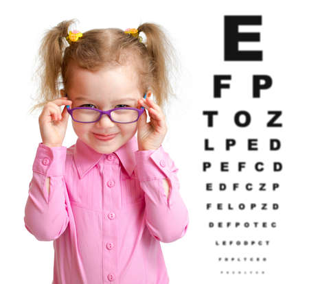 girl glasses: Smiling girl putting on glasses with blurry eye chart behind her