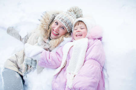 Happy mother and child have fun on snow in winter outdoor