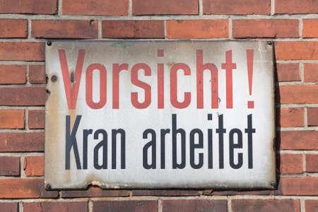 Vorsicht Kran arbeitet retro sign on brick wall photo