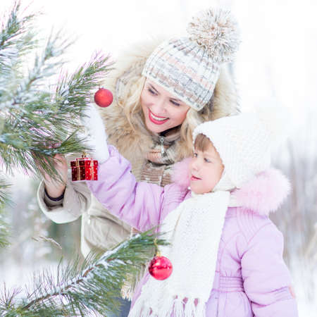decorating christmas tree: Happy mother and child decorating christmas tree outdoor wintertime
