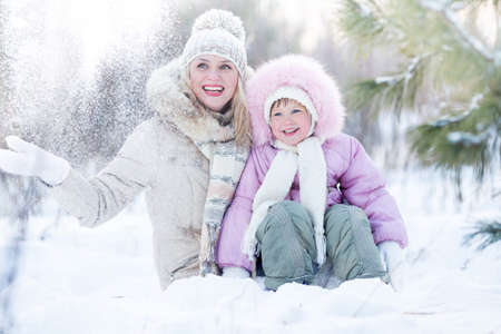 joy of life: Happy family mother and daughter sitting in snow outdoor wintertime Stock Photo