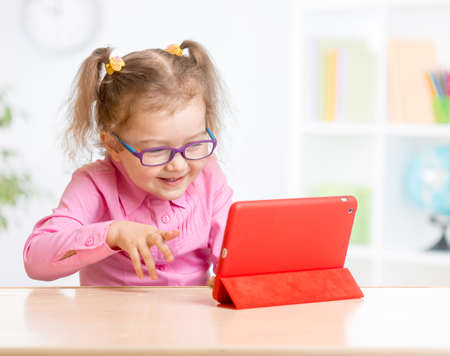 Kid with tablet PC in glasses learning with interest