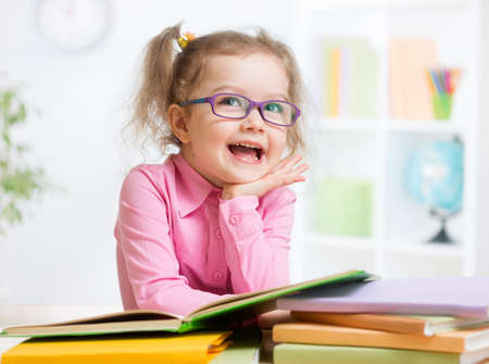 little child: Happy kid reading books and dreaming Stock Photo