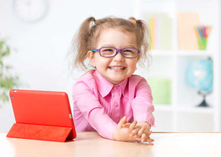 early childhood: Happy kid with tablet PC in glasses as early education concept