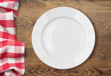 white empty dinner plate setting on wooden table with tablecloth Stock Photo
