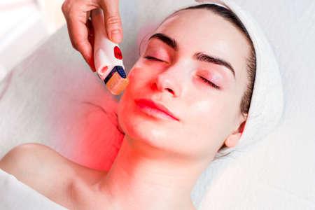 Microneedle gezicht mesotherapie met rood licht Stockfoto