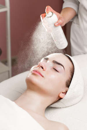 serum mask spraying from can on young womans face in spa salon photo