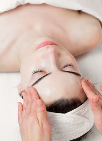 Young woman head and face massage in spa salon photo