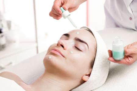 mujer maquillandose: Tratamiento facial Serum de la mujer joven en sal�n del balneario