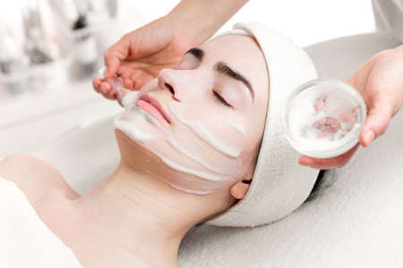 facial cleansing: Young woman peeling foam mask applying on face