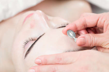 Serum capsule in front of young woman face in spa salon photo