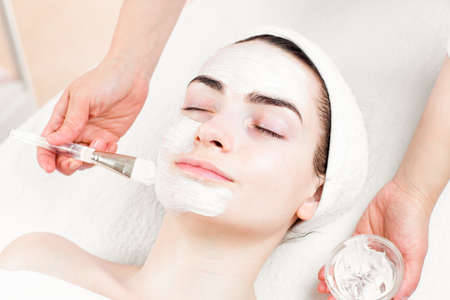 dayspa: Young woman facial mask applying in beauty parlour Stock Photo