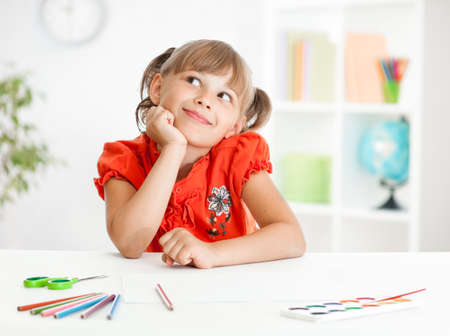 child classroom: Smiling cute schoolgirl dreaming making homework. Creation concept. Stock Photo