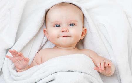 Lindo bebé sonriente divertido acostado sobre la espalda en una toalla de baño