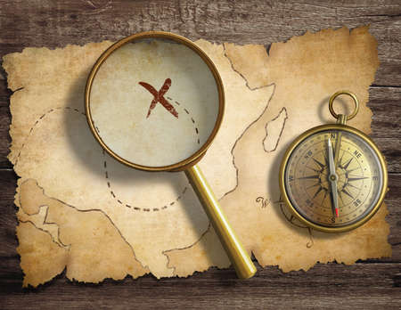 aged antique nautical compass and magnifying glass on table with treasure map Stock Photo