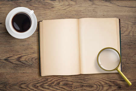 Diary or open book with loupe and coffee cup. photo
