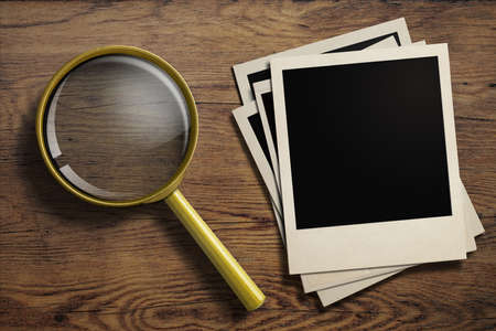 magnifying glass or loupe with old photo frames stack on wood table Stock Photo