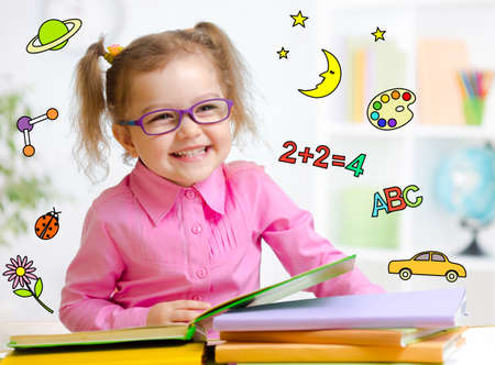 early education: Happy child in glasses reading book. Early education in kindergarten concept.