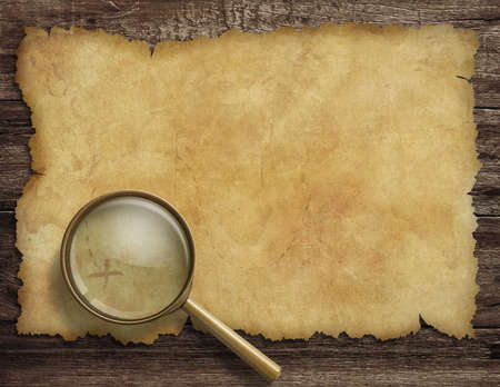 old treasure map on wooden desk with magnifying glass photo