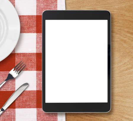 black tablet pc on dinner table with blank screen photo