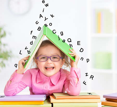 early education: Smart smiling kid in glasses taking refuge under book roof from falling letters Stock Photo