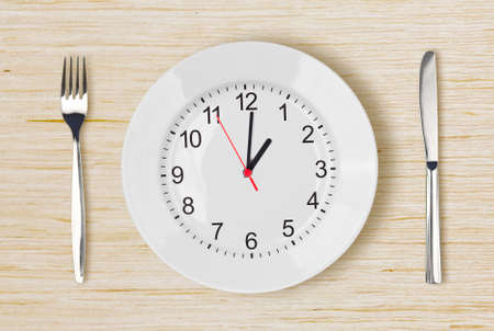 Dinner plate with clock face on wooden table with fork an knife