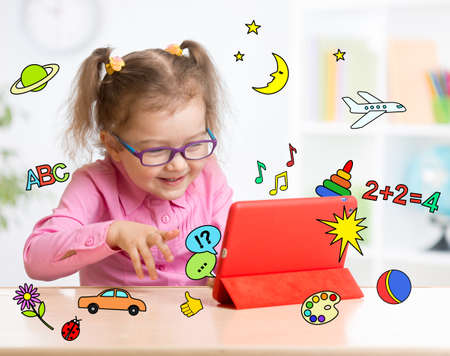 early education: Kid with tablet computer in glasses. Early education. Stock Photo