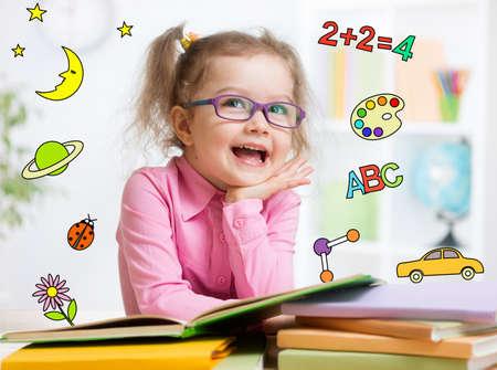 Prodigy: Śmieszne inteligentny dzieciak w okularach czyta książkę w przedszkolu