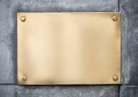 blank gold or brass metal sign or nameboard on concrete wall Stock Photo
