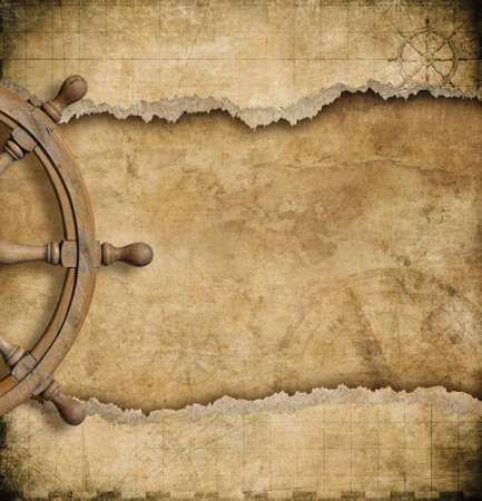 steering wheel and torn vintage nautical map Foto de archivo