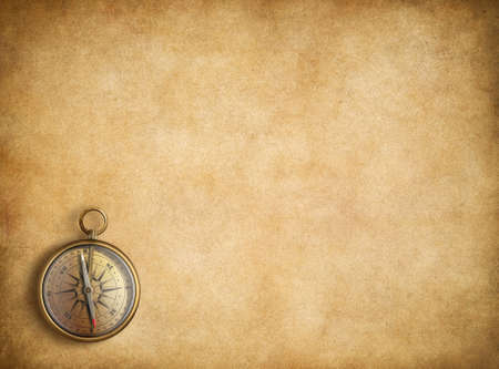 Brass compass on blank vintage paper background 스톡 콘텐츠