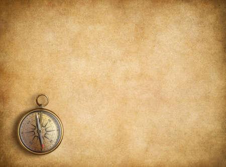 Brass compass on blank vintage paper background Foto de archivo