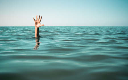 drown: Hand in sea water asking for help. Failure and rescue concept.