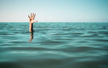to drown: Mano en el agua de mar pidiendo ayuda. El fracaso y el concepto de rescate.