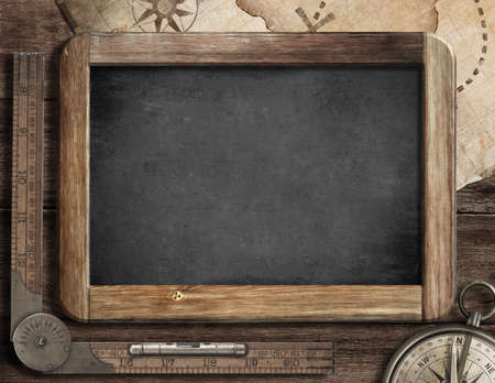 travel features: Vintage blackboard with treasure map, old compass and ruler. Adventure and discovery concept. Stock Photo