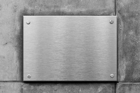nameboard: blank metal sign or nameboard on concrete wall Stock Photo