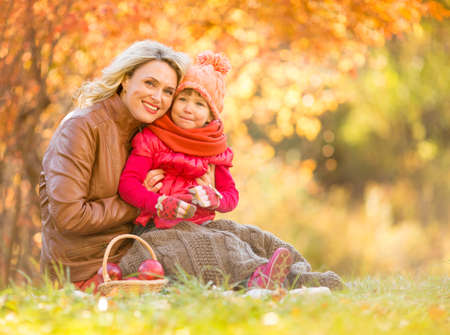 family outside: Happy mother and child sitting outdoor in autumn