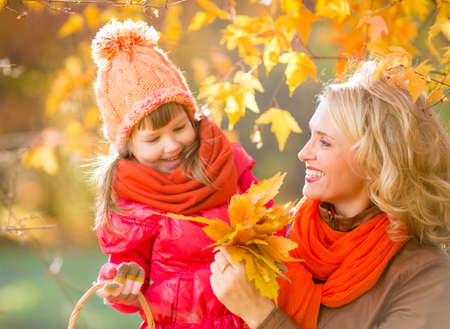 fall leaves: Smiling mother and kid outdoor with autumn yellow leaves