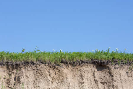 gully: Ravine or gully cut with soil, grass and blue sky Stock Photo