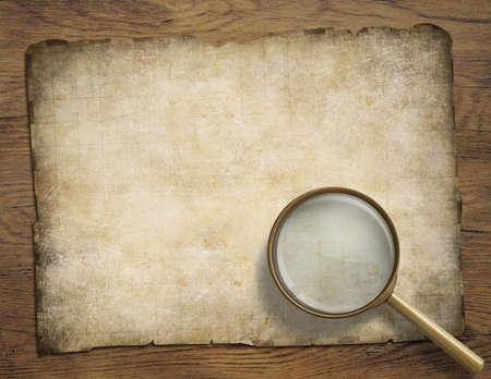 boarded: old navigation map or parchment on wooden desk with magnifying glass Stock Photo