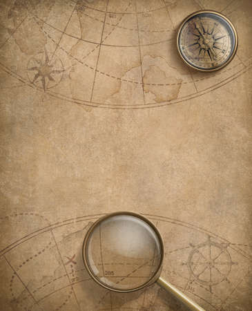 aged compass and magnifying glass over nautical map