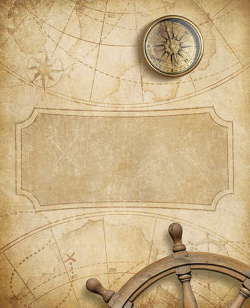 aged compass and steering wheel over nautical map Archivio Fotografico