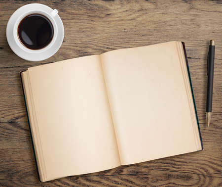 Open book and coffee cup on old wooden table with pen