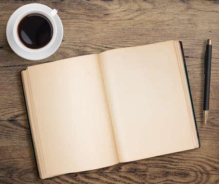 kniha: Otevřená kniha a šálek kávy na starém dřevěném stole s perem