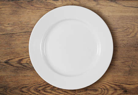 white empty dinner plate on wooden table surface Stock Photo
